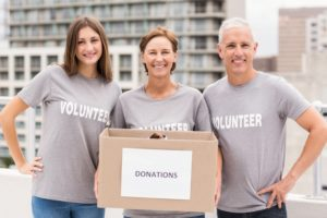 Smiling volunteers holding donation box